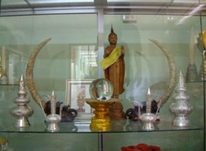 In the backgound a carved Sandelwood Buddah flanked By two white bull elephant Tusks, various silver urns and Chalices.